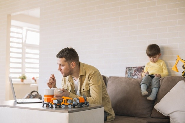 Padre en teletrabajo junto a su hijo